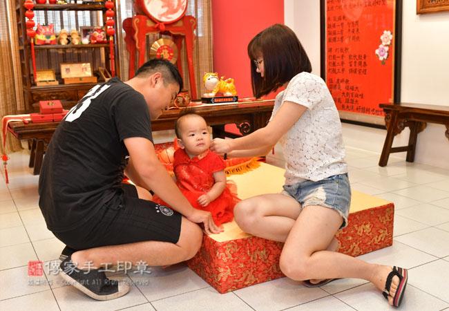爸媽正在給寶貝穿抓周古裝照