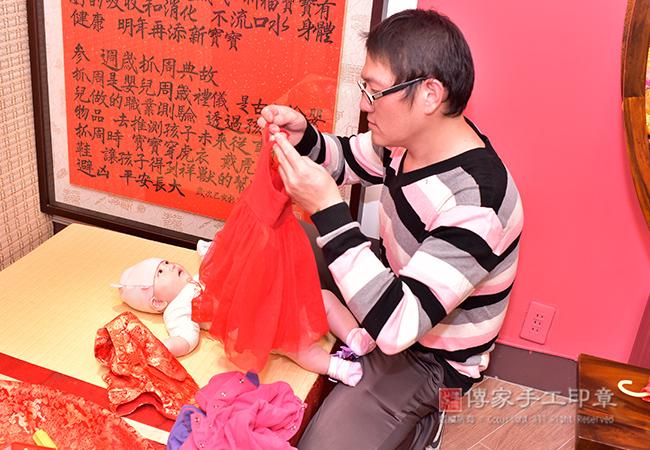 爸爸幫寶寶穿吉祥古禮服圖