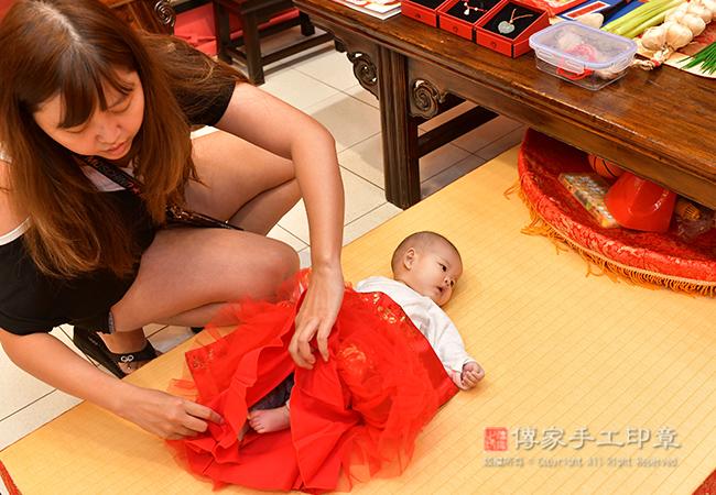 媽媽正在給寶貝換上四月收涎的古裝禮服照
